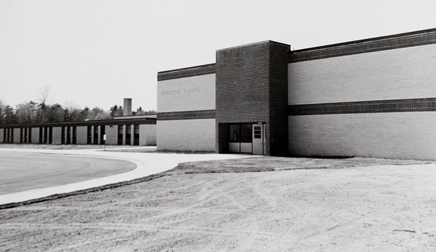 Black and white photograph of the front of Riverside Elementary School facing Old Mount Vernon Road taken in 1968. The picture was taken during the fall because in the distance some of the trees have started to lose their leaves. The grounds in front of the building are still being sodded.