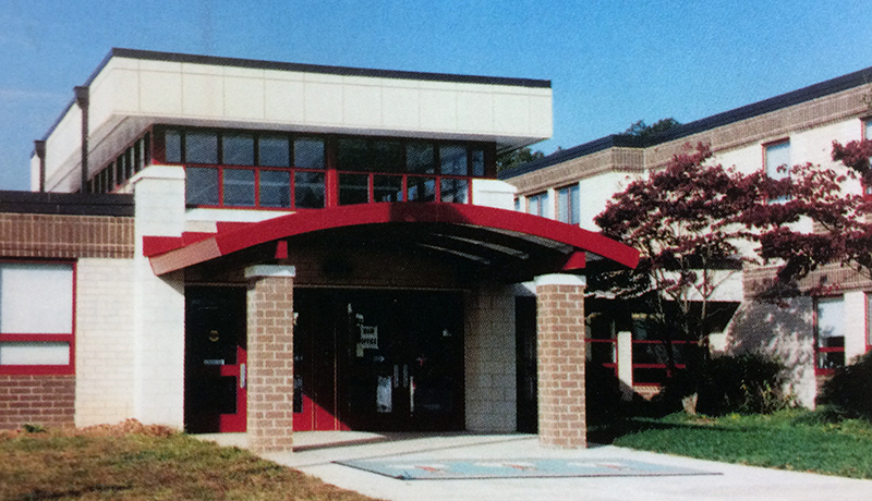 Color photograph of the main entrance to Riverside Elementary School from our 2004 to 2005 yearbook. The school has been newly renovated and the entrance awning is painted a bright red.