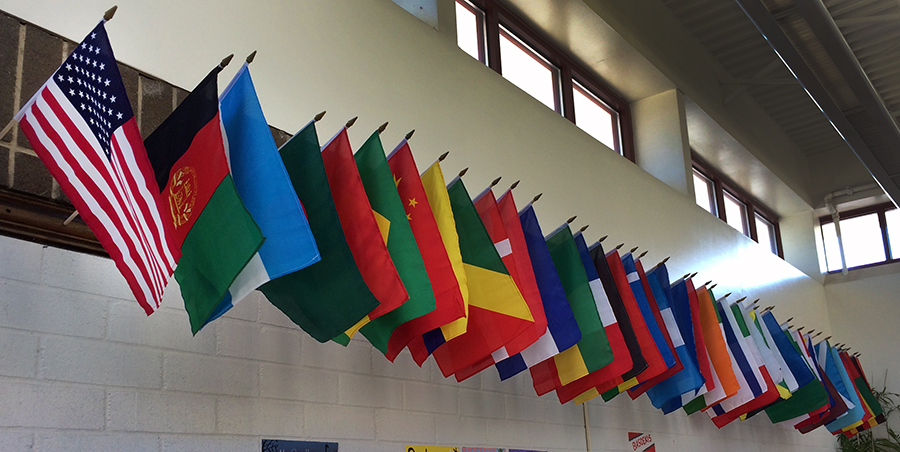 Photograph of the flags hanging in our main lobby. The American flag is on the far left. At least 41 nations are represented.