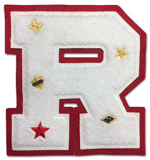 A white felt letter R is set against a red felt background. On the letter are five small pins, a letter K, a gold star, a red star, a badge with the word kindness printed on it, and a diamond with the letters TV in the center.